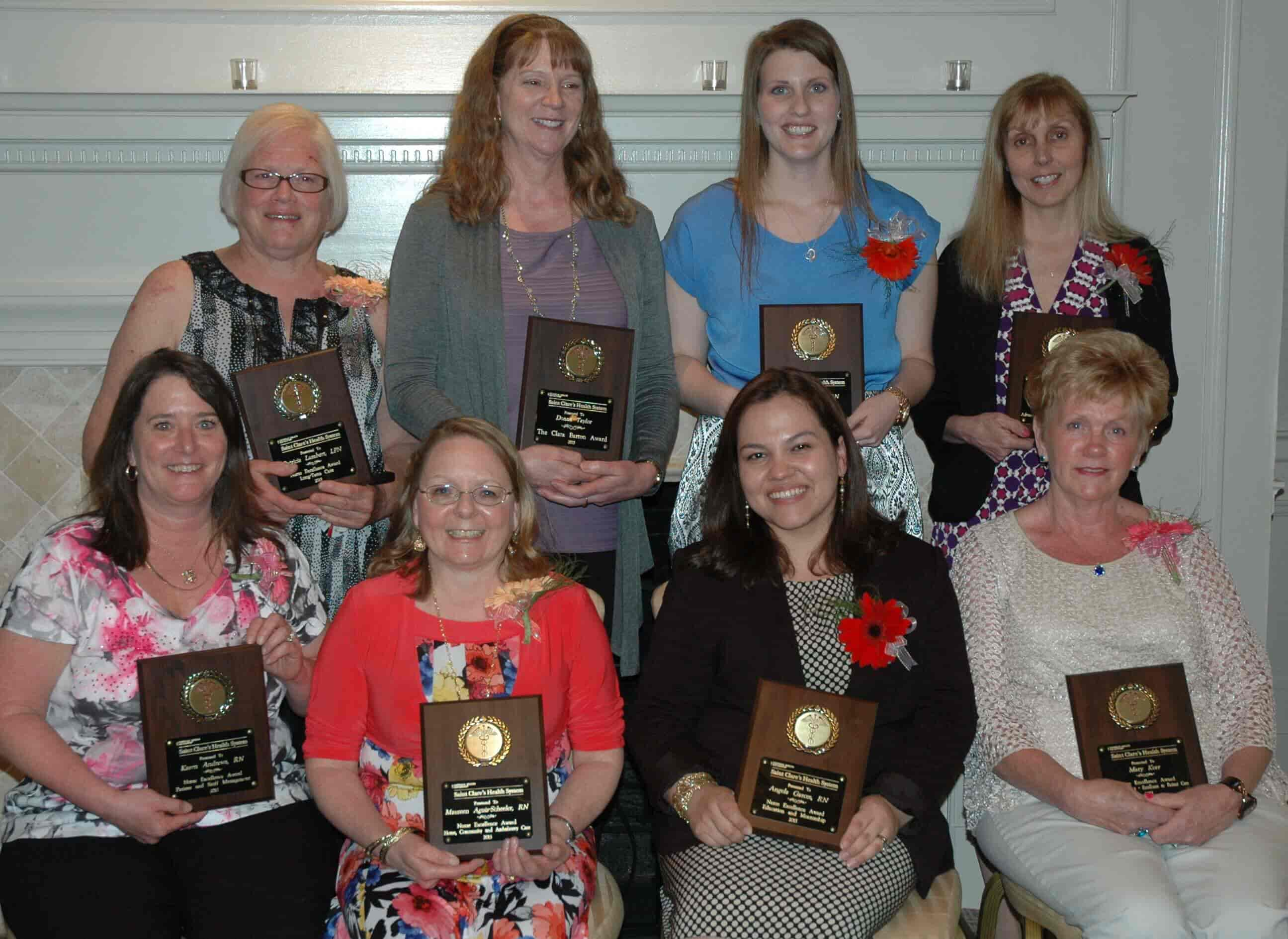 Group of 8 nurses holding excellence award